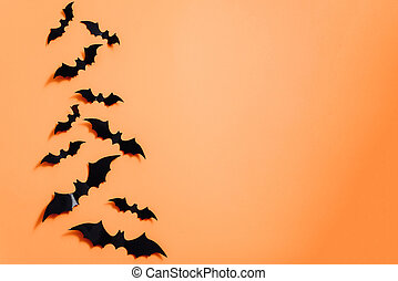 Artificial bats on an orange background. Halloween concept. Flat lay, top view, copy space
