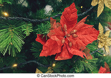 Artificial Christmas tree and red poinsettia flower