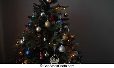 artificial christmas tree with shining garlands in darkness...