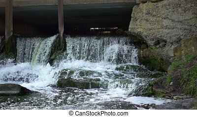 Artificial dam waterfall in slow motion. Water flows and...