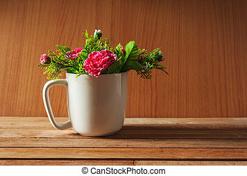 Artificial flower in cup on wooden