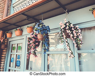 Artificial flowers against the windows of an old building in old Tbilisi
