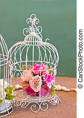 Artificial flowers bunch in white birdcage.