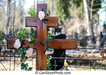 Artificial flowers garland or wreath of roses on the cross on the grave in the spring. Cemetery decorations.