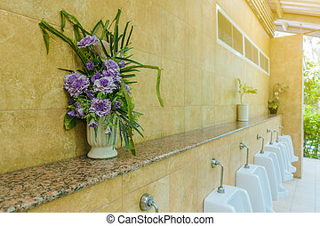 Artificial flowers in pots for decoration placed on the shelf above the urinal
