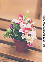 Artificial Flowers In Vase On Wooden Table