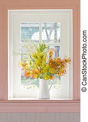Artificial flowers in white vase beside white window.