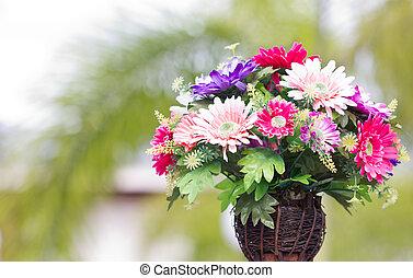 Artificial flowers in wooden vase.