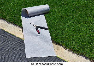Artificial grass turf installation in garden with tools