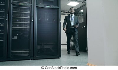 Man coming up to supercomputer processor and inspecting it