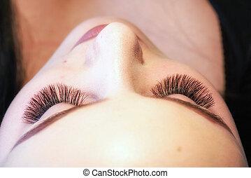 Artificial 4D lashes. Eyelash extension procedure. Close up view