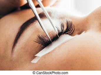 Artificial lashes. eyelash extension. - Beautician making 4D...