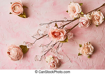 Artificial pink flowers arrangement on pink colored background