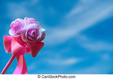 Artificial pink rose against blue sky