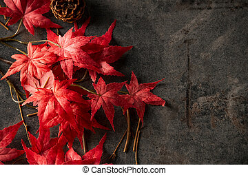 Artificial red maple leaves on dark stone background.