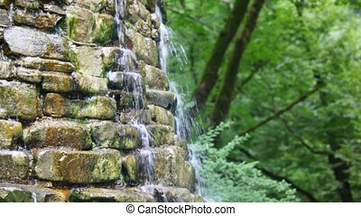 artificial stone cascades waterfall fountain in park,...
