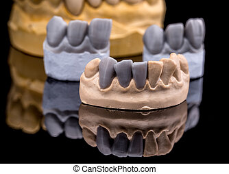Artificial tooth, wax models on black background