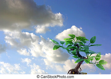 Artificial tree on dramatic sky with clouds
