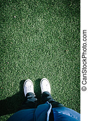 Artificial turf grass on sports field with two shoes, personal perspective from above