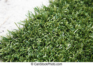 Artificial turf - Artificial lawn on white sand.