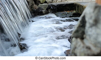artificial waterfall in a pond with clear water