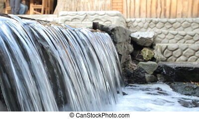Artificial waterfall in a pond with stone