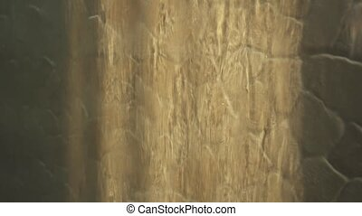 Artificial waterfall on the background of stone wall -...