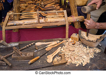 Artisan  hands at work, carving wood into spoons