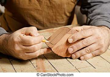 Artisan hands sketching on wood billet at workbench
