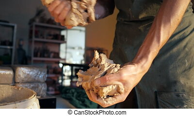 Artisan potter prepares material clay for pottery. Man knead...