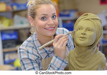 artisan woman finishing sculpture in a studio