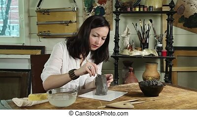 Artisan woman shaping clay sculpture in a studio
