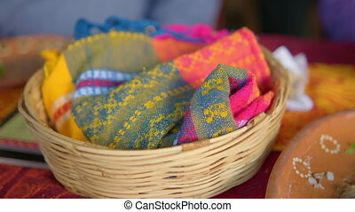 Close-up of artisanal tortilla napkin and basket above beautiful red and orange tablecloth. Colorful napkin in traditional palm basket above artistic Hispanic table. Mexican cuisine and handcrafts