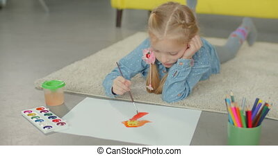 Artist adorable girl painting on the floor - Creative...