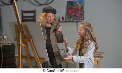 Artist and girl discuss the future picture in the studio