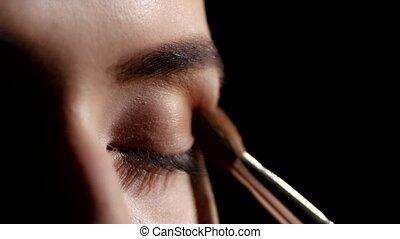 Artist applying eyeshadows. Black. Makeup. Closeup