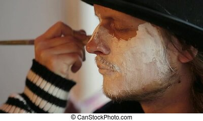 Artist Applying Makeup Onto Man's Face At Halloween
