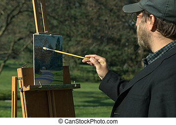 artist at work - accomplished artist creating landscape in...