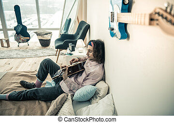 Focused unusual young man resting in bedroom with guitar