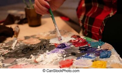Artist brush mixing oil color painting on palette.