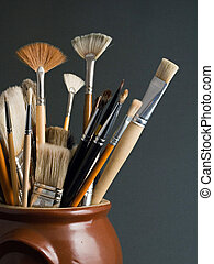 Artist brushes in a pot, on a dark grey background