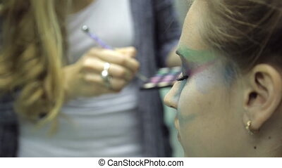 Artist does make-up on young girl, close up, body-art.