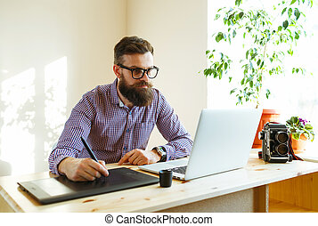Artist drawing something on graphic tablet at the home office