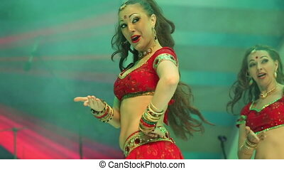 girl dancing on stage in a red national Indian suit