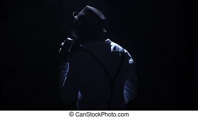 Artist in the hat a weak light at the microphone singing the song. Black background. Silhouette. Slow motion. Close up