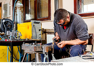Artist is making figure by welding few metal wires in his workshop, barehanded