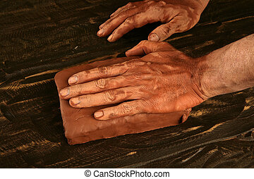 artist man hands working red clay for handcraft