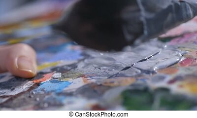 Artist mixing acrylic paints with palette knife - Detail of...