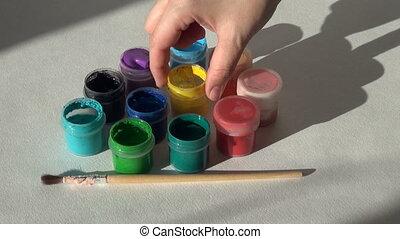 artist opens jars of gouache acrylic paint. Homework, the...
