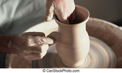Artist operates hands, which gently creating correctly shaped handmade from clay. Traditional pottery making, teacher shows the basics of pottery in art studio